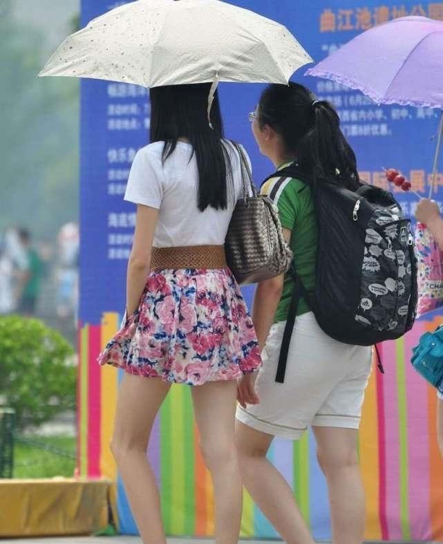 街拍美女:打着太阳伞逛街的短裙长腿美女
