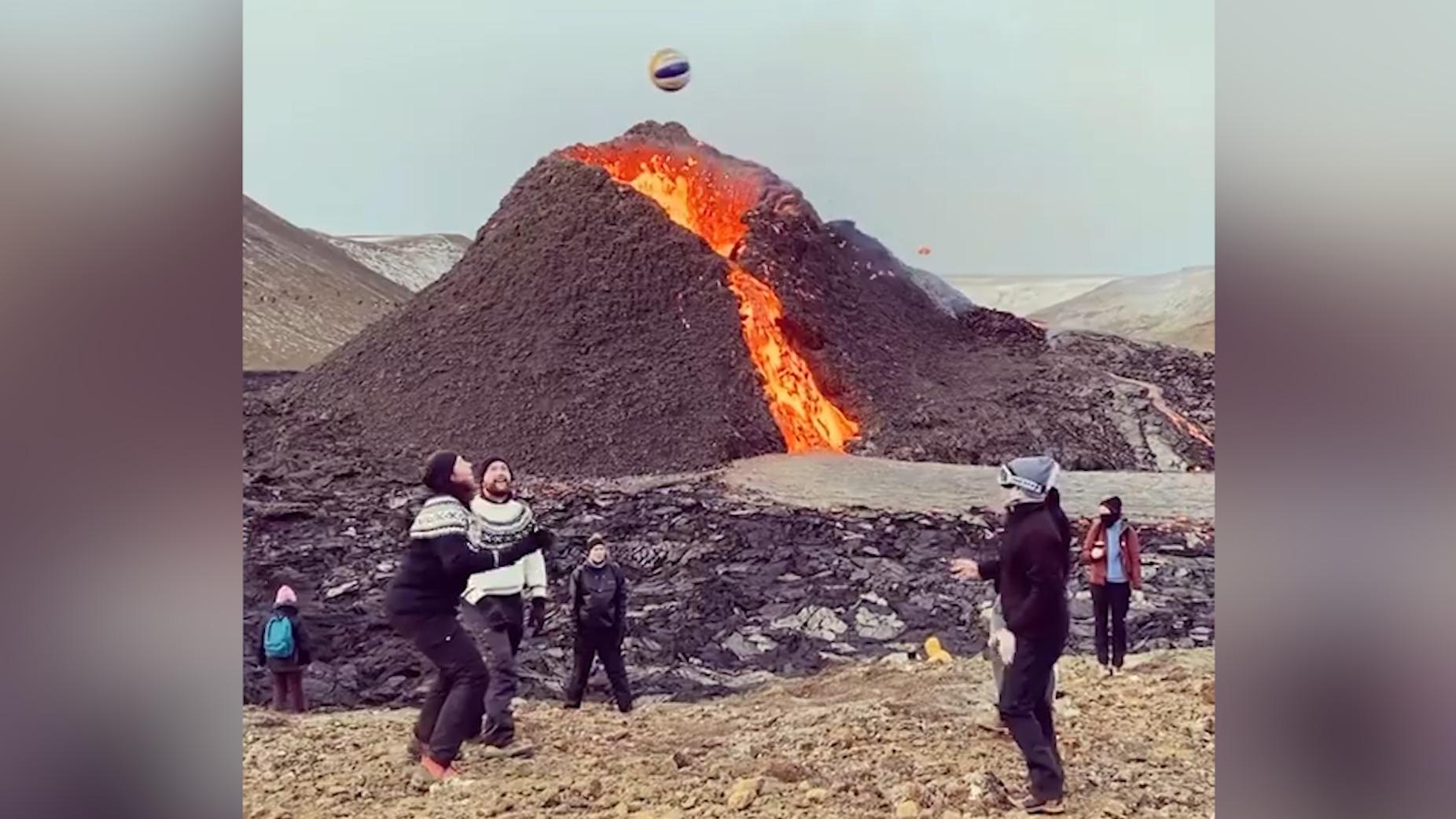 冰岛火山熔岩喷发不断 游客一旁淡定打排球