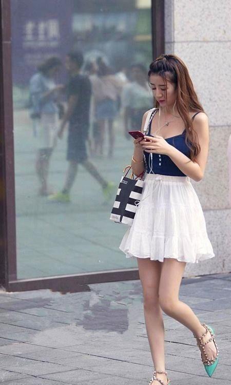 街拍:小姐姐一件白色单肩背心搭配低腰牛仔短裤,尽显时尚魅力插图(2)